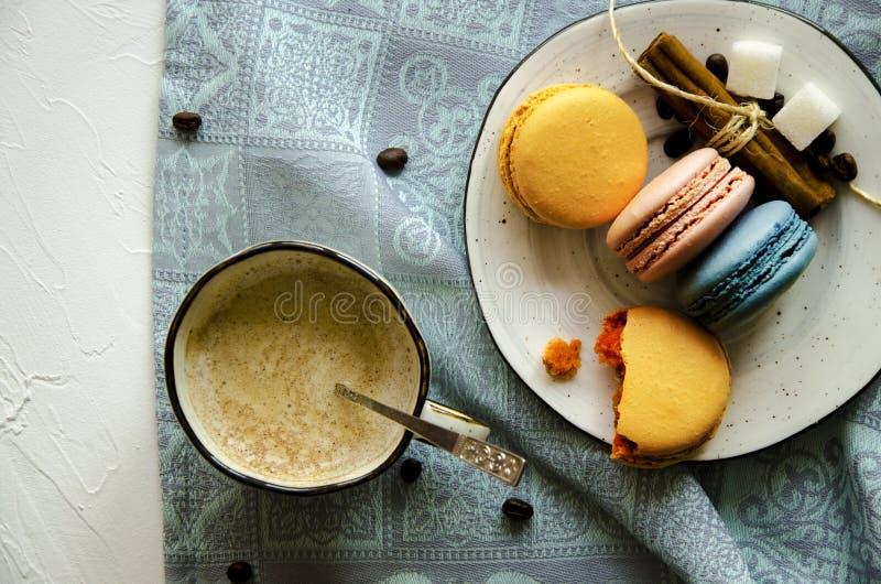 Una taza de capuchino caliente con canela y macarrones multicolores de la torta foto de archivo libre de regalías