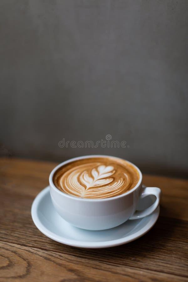 Una taza de capuchino con arte del latte imagenes de archivo