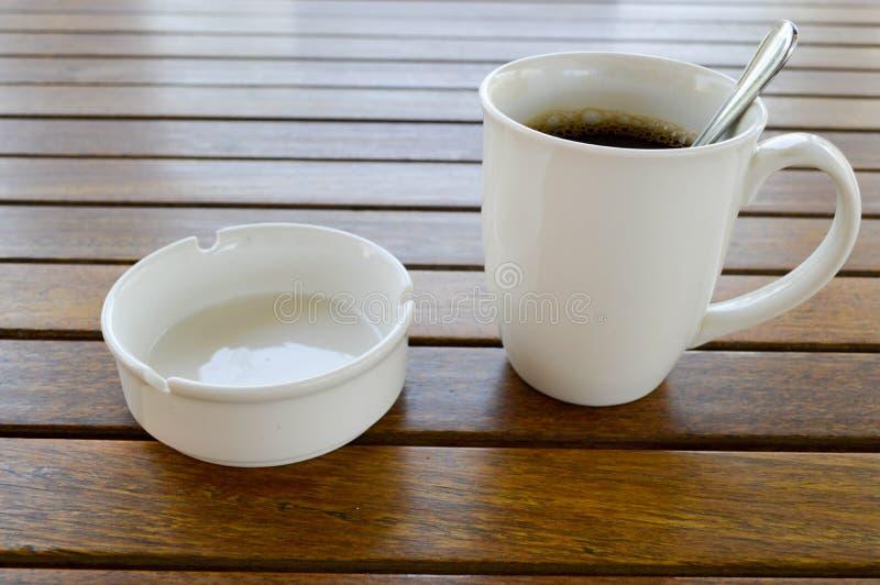 Una taza de cerámica blanca con una mañana que restaura el café caliente con la cucharilla brillante de la bebida del té y del té imagenes de archivo