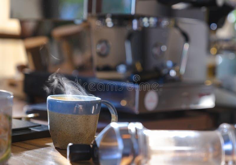 una taza de cerámica de café caliente del humo en la tabla de madera con la máquina borrosa del café en fondo foto de archivo libre de regalías
