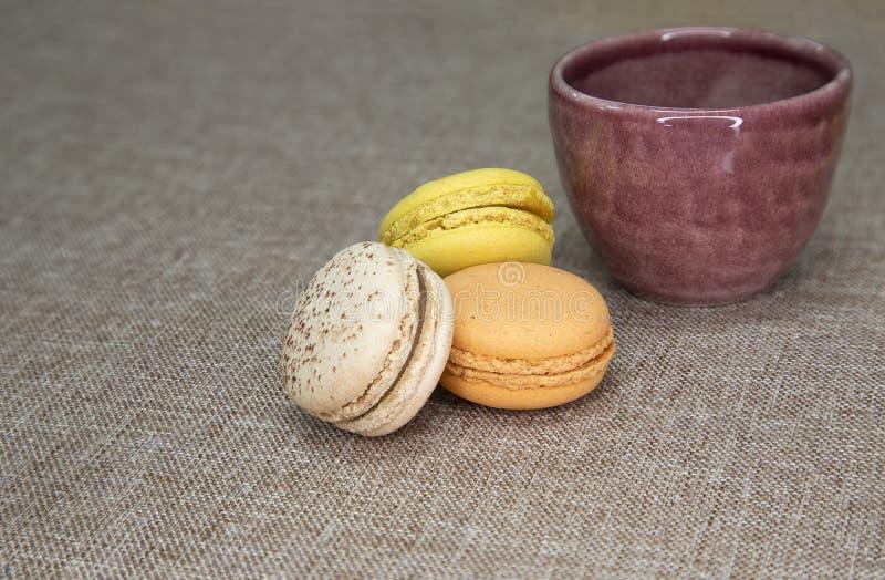 una taza de cerámica púrpura y macarrones imagen de archivo