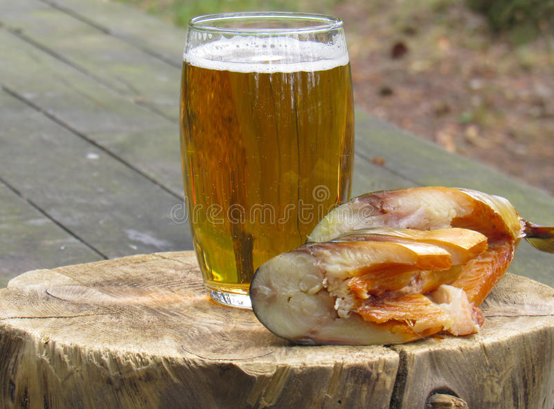 Una taza de cerveza con un pescado imagen de archivo