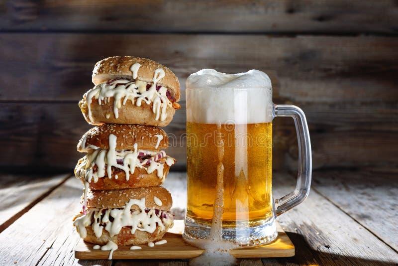 Una taza de cerveza ligera y de una hamburguesa enorme imagenes de archivo