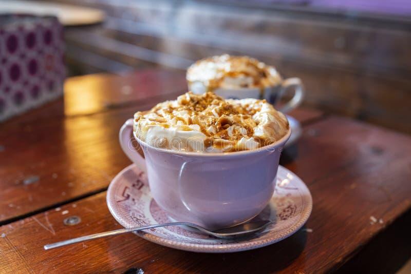 Una taza de chocolate caliente fresco rematado con crema azotada y caramelo salado imagen de archivo libre de regalías