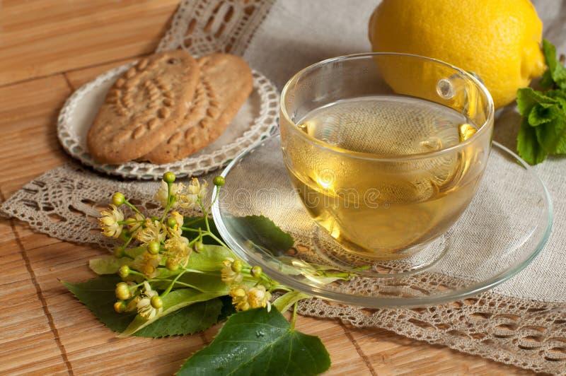 Una taza de cristal de té de la flor de la cal, de galletas y de un limón maduro en una superficie de madera foto de archivo