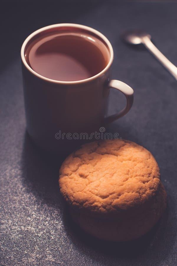 Una taza de cristal de té negro con las galletas En un fondo de mármol grisáceo oscuro imagen de archivo libre de regalías