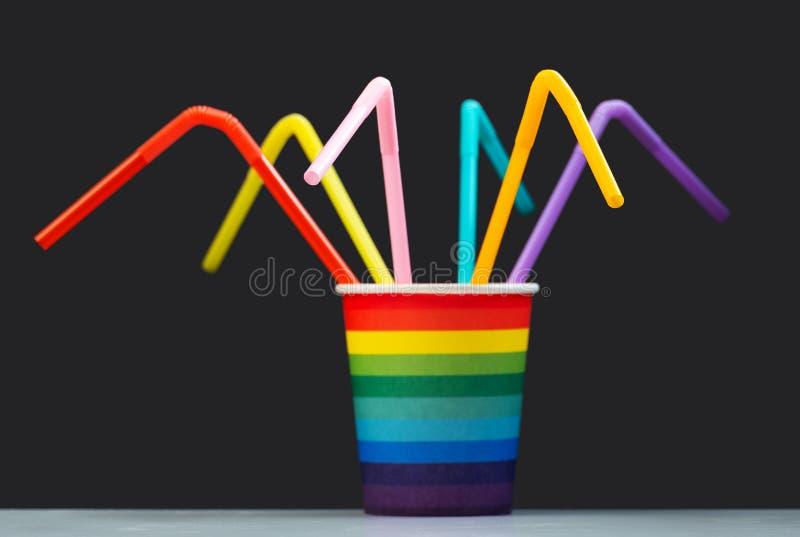 Una taza de papel del color como un arco iris con muchos tubos multicolores del cóctel en un fondo gris Foco selectivo r imagen de archivo libre de regalías