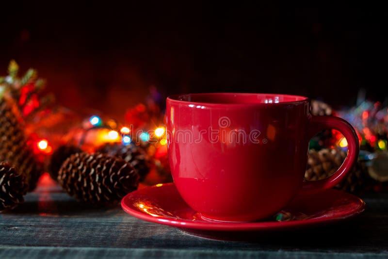 Una taza de soportes del café en el fondo de las luces de la Navidad fotos de archivo
