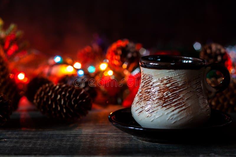 Una taza de soportes del café en el fondo de las luces de la Navidad foto de archivo libre de regalías