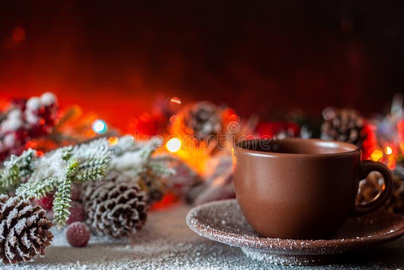 Una taza de soportes del café en el fondo de las luces de la Navidad fotos de archivo libres de regalías