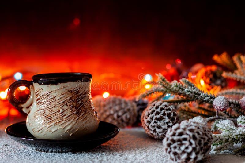 Una taza de soportes del café en el fondo de las luces de la Navidad fotografía de archivo