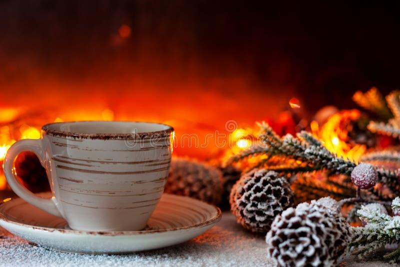 Una taza de soportes del café en el fondo de las luces de la Navidad imagenes de archivo