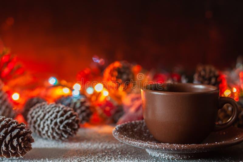 Una taza de soportes del café en el fondo de las luces de la Navidad imágenes de archivo libres de regalías