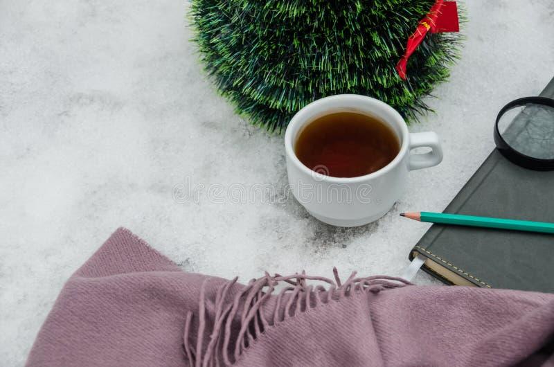 Una taza de té, de una bufanda, de una lupa, de un lápiz, de un cuaderno y de un pequeño árbol de navidad artificial contra la pe foto de archivo libre de regalías