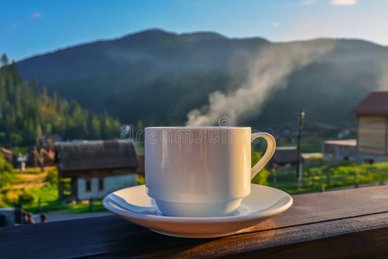 Una taza de té, café, colocándose en el pórtico del balcón del hotel, pasando por alto las montañas, en la madrugada en la luz de fotos de archivo