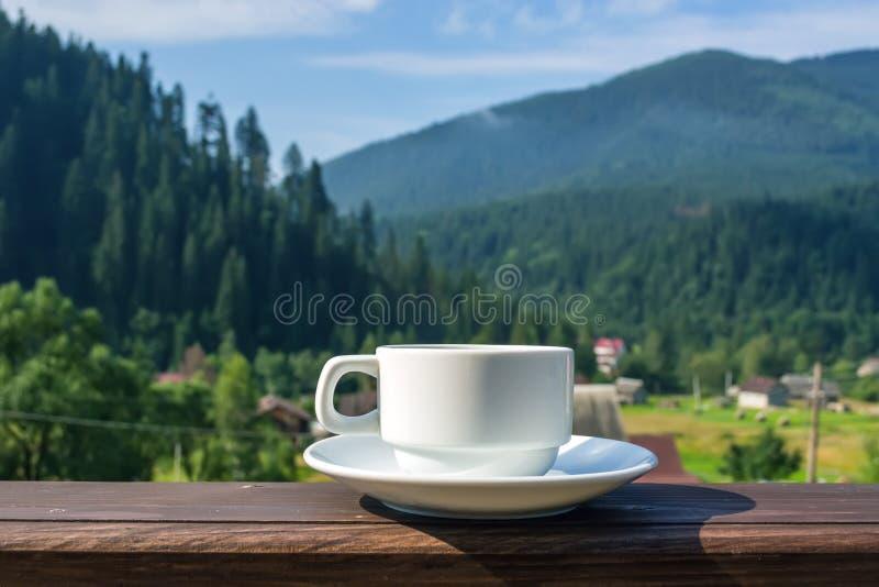 Una taza de té, café, colocándose en el pórtico del balcón del hotel, pasando por alto las montañas, en la madrugada en la luz de imagenes de archivo
