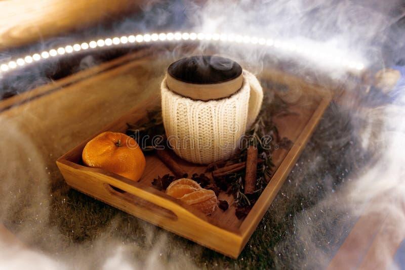 Una taza de té caliente con los pedazos de manadarines en una bandeja de madera en el humo fotos de archivo