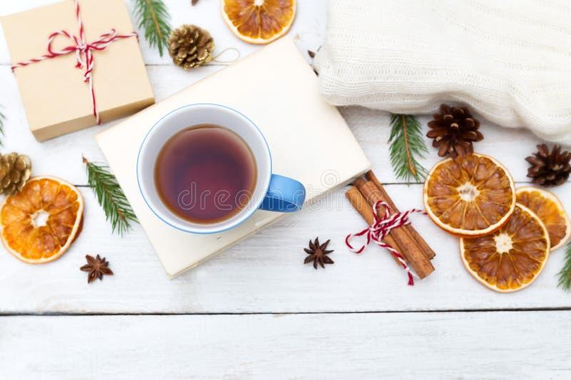 Una taza de té caliente está en el libro, y alrededor de los decoros de la Navidad fotos de archivo libres de regalías