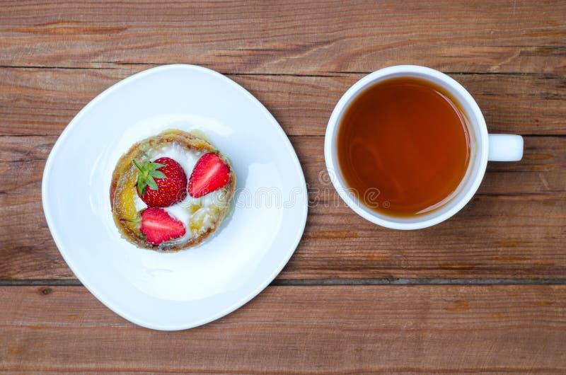 Una taza de té caliente y de un postre con las fresas en una etiqueta de madera imagen de archivo libre de regalías