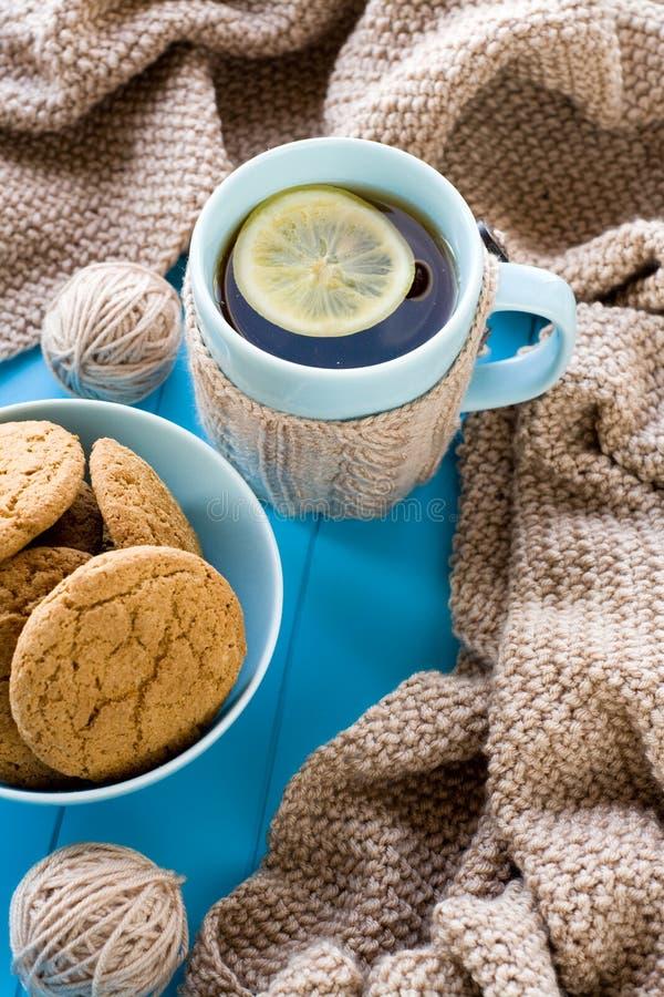 Una taza de té con el limón, galletas, beige hizo punto la manta fotografía de archivo libre de regalías