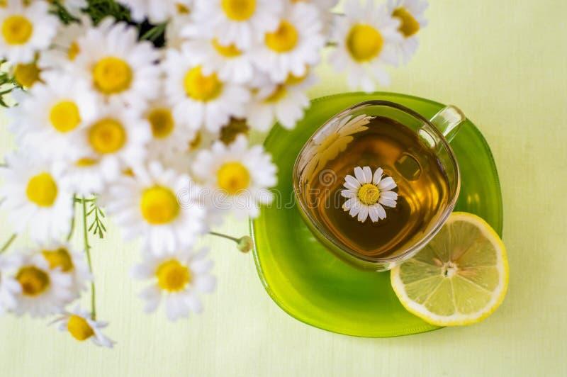 Una taza de té de manzanilla y un ramo de margaritas foto de archivo