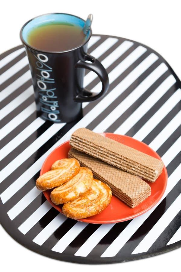 Una taza de té, de tortas y de obleas foto de archivo libre de regalías