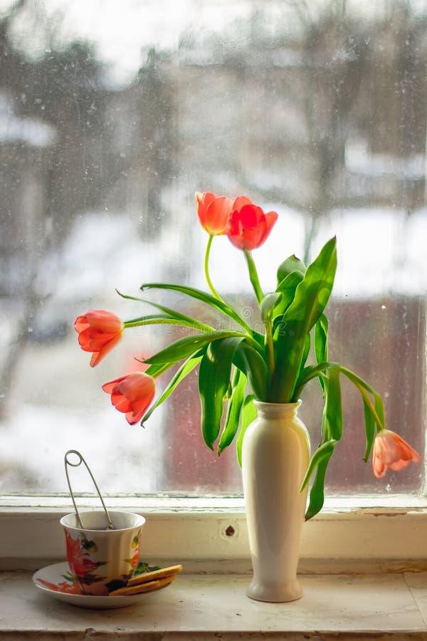 Una taza de té en el alféizar y las flores imagen de archivo