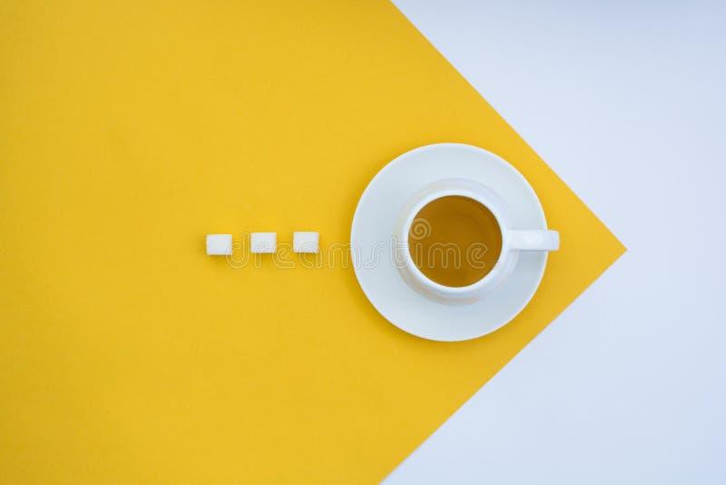 Una taza de t? en un fondo del amarillo y blanco fotos de archivo libres de regalías