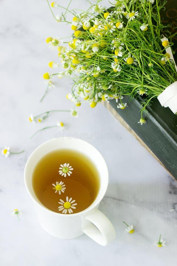 Una taza de té de manzanilla calmante útil, un ramo de margaritas y libros en una tabla de mármol foto de archivo libre de regalías