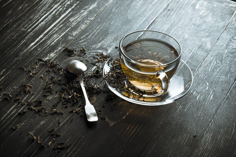 Una taza de té negro con la cuchara imagen de archivo libre de regalías