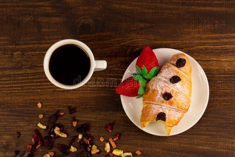 Una taza de té negro con las frutas secas, el cruasán con la fresa y el fondo de madera de la tabla Wiev superior imagenes de archivo