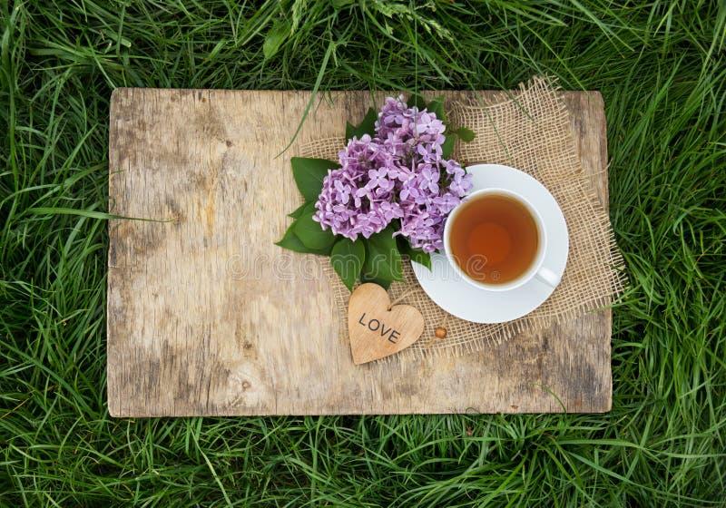 Una taza de té negro y flores de lilas fragantes en un viejo tablero de madera Té en el jardín fotografía de archivo