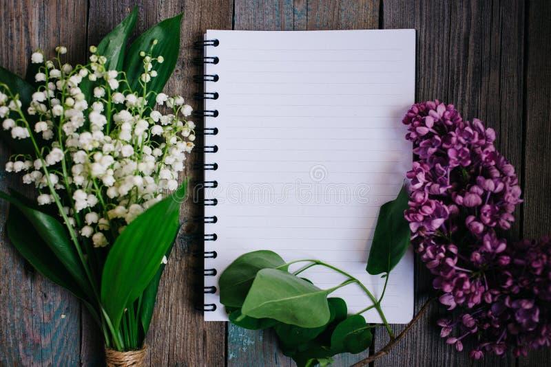 una taza de té, de nueces, de lilas y de un cuaderno en una tabla de madera imagen de archivo