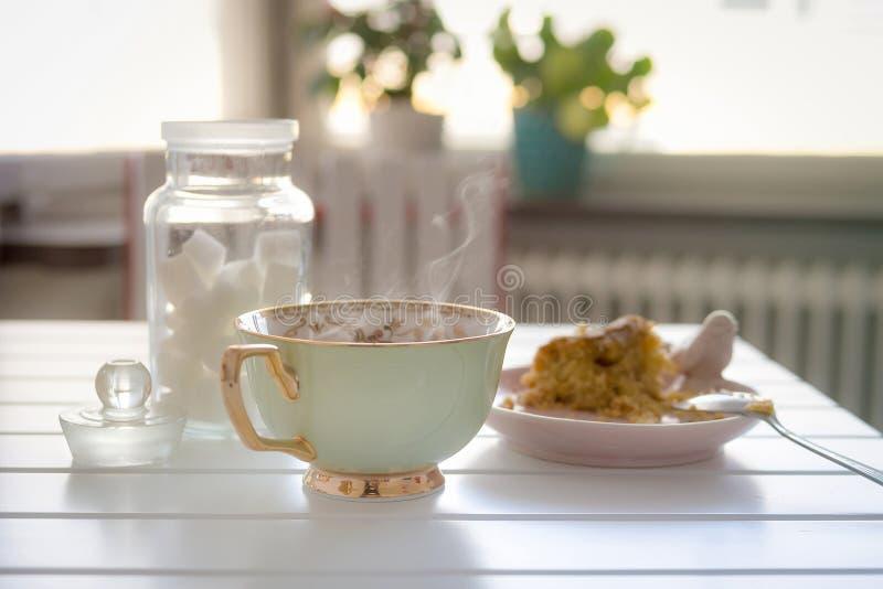 Una taza de té o de café caliente con una torta en la tabla imagenes de archivo