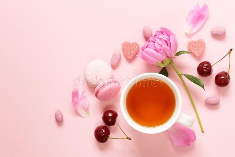 Una taza de té para una mujer, los macarrones, las flores y los dulces fotografía de archivo
