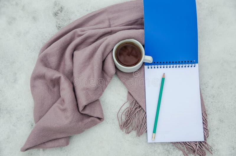 Una taza de té, de un cuaderno, de un lápiz y de una bufanda imagen de archivo