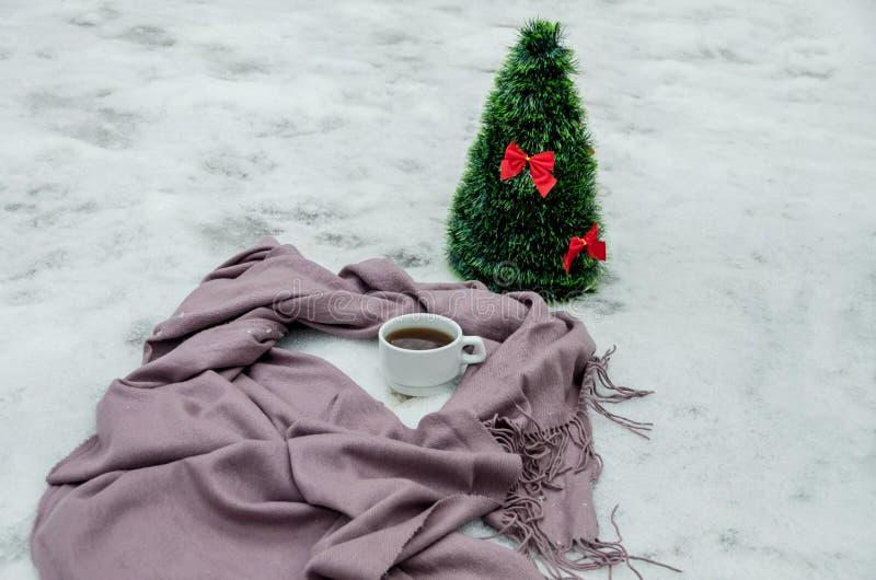 Una taza de té, un scarfand un pequeño árbol de navidad artificial imágenes de archivo libres de regalías