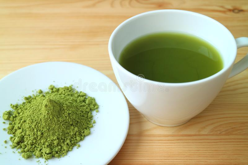 Una taza de té verde caliente de Matcha con una pequeña placa del polvo del té de Matcha foto de archivo libre de regalías
