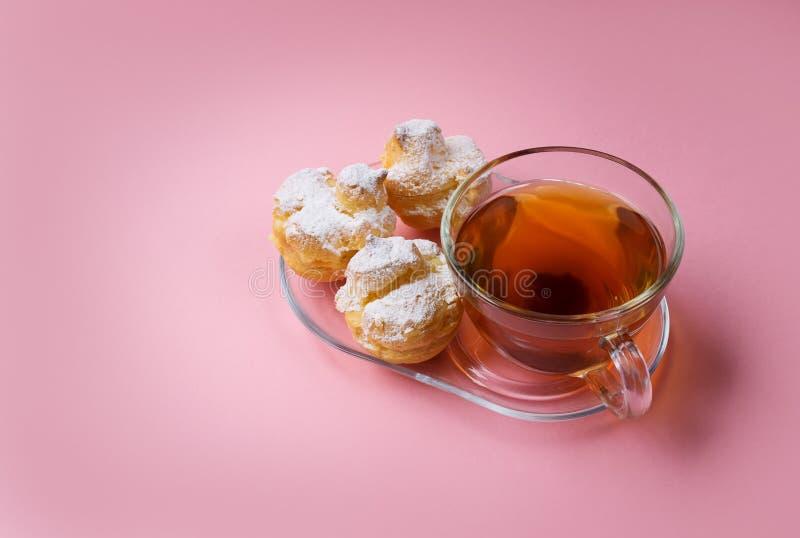 Una taza de té verde y tres de profiteroles asperjados con el polvo del azúcar en un fondo rosado imagen de archivo libre de regalías