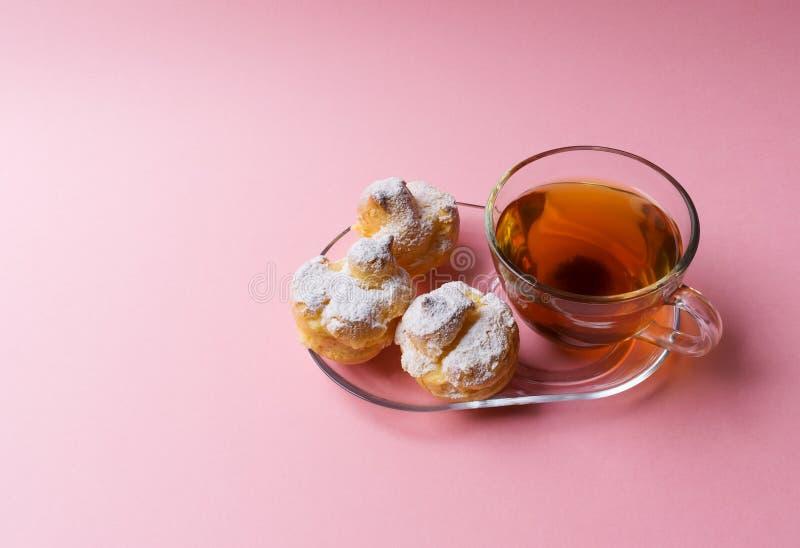 Una taza de té verde y tres de profiteroles asperjados con el polvo del azúcar en un fondo rosado fotografía de archivo libre de regalías