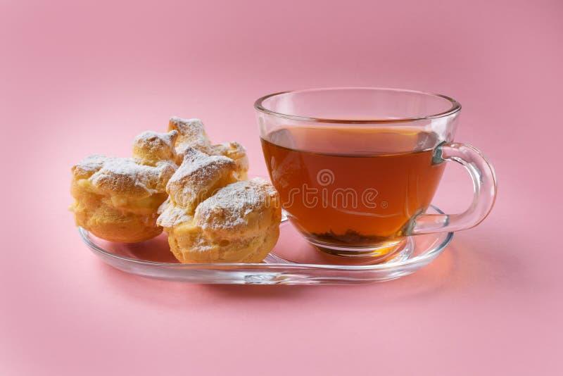 Una taza de té verde y tres de profiteroles asperjados con el polvo del azúcar en un fondo rosado imagenes de archivo