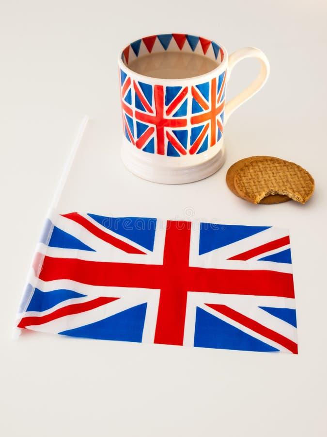 Una taza de té y de galletas ingleses con una bandera fotografía de archivo