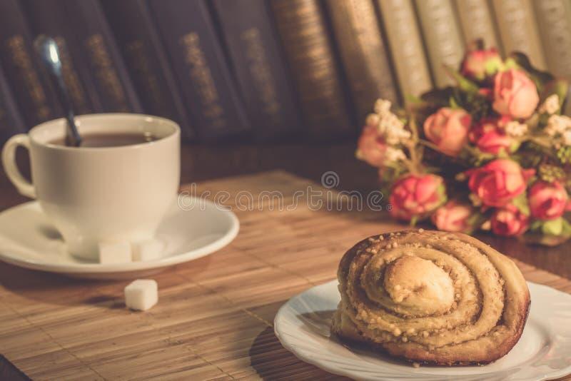 Una taza de té y una placa con los pasteles foto de archivo