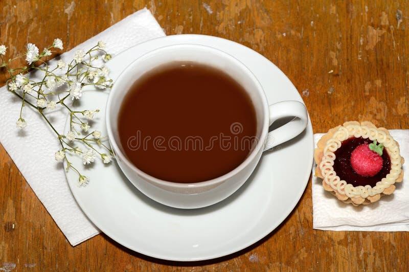 Una taza de witn del té una flor y un postre imagen de archivo