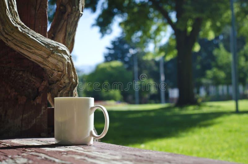 Una taza en blanco del café con leche en el banco con los registros torcidos foto de archivo