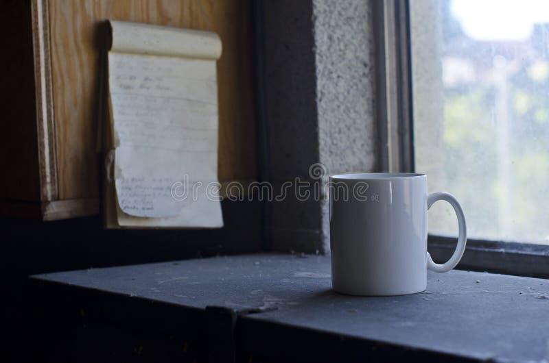 Una taza en blanco del café con leche y la lista de tarea fotografía de archivo