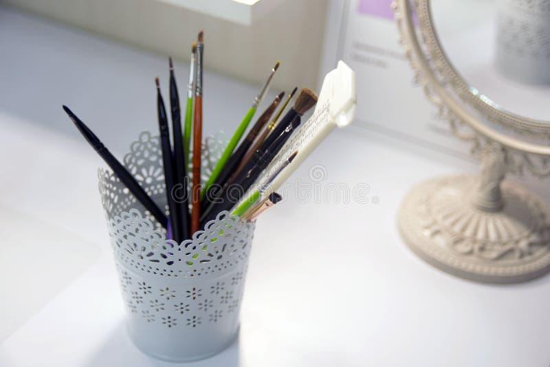 Una taza hermosa, blanca con los modelos a cielo abierto para almacenar los cepillos para compone fotos de archivo libres de regalías
