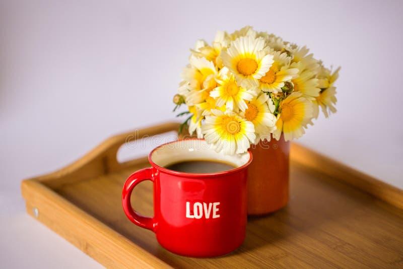 Una taza roja con la palabra 'amor 'con café/té caliente y un ramo de margaritas en una bandeja de madera imagenes de archivo