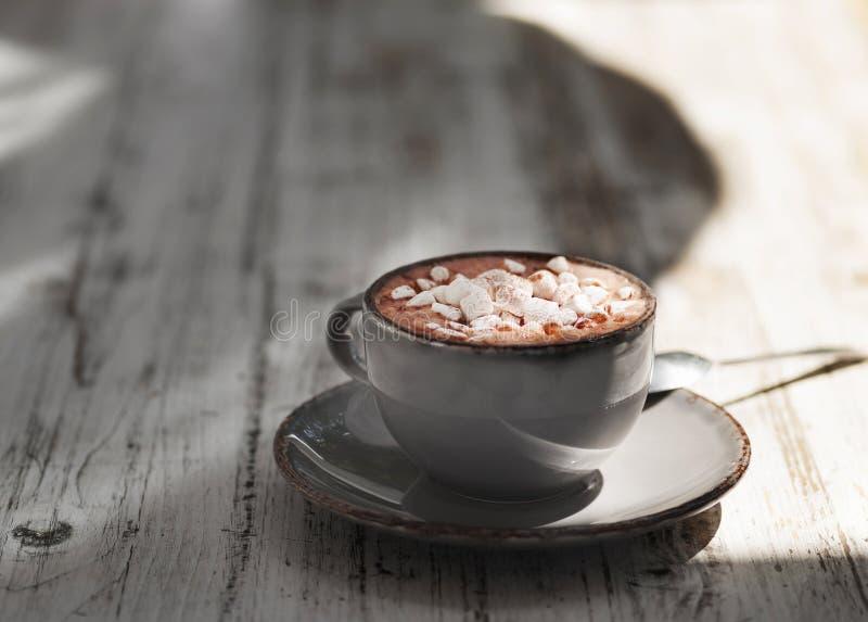 Una tazza antica del latte del latte con le caramelle gommosa e molle su un fondo di legno grigio Una bevanda dolce in una tazza  immagine stock