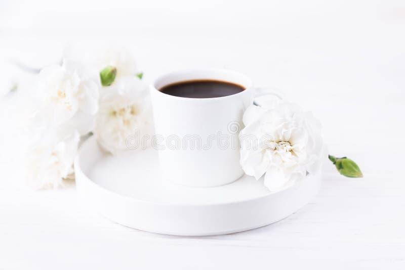 Una tazza bianca di caffè nero e dei fiori di garofano su fondo bianco, uno spazio di copia fotografie stock